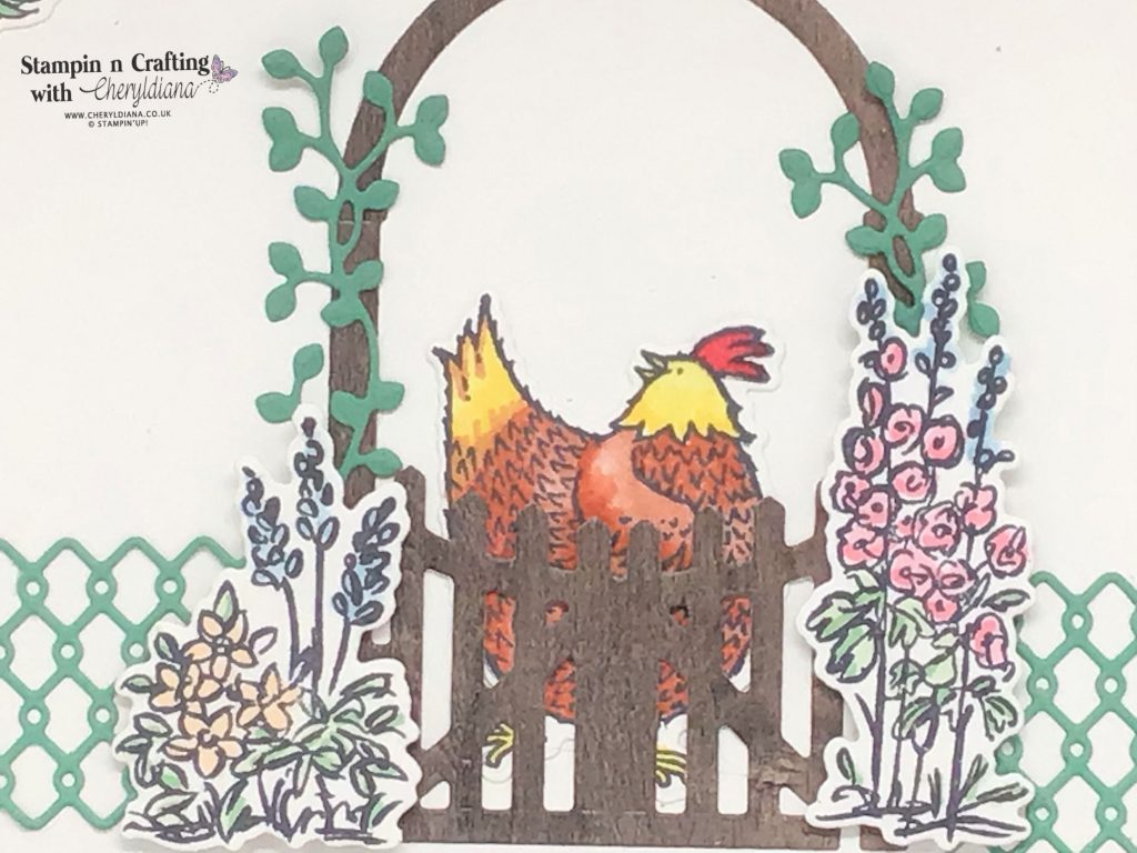 Photo of die cut fencing, gate, chicken and flowers for bottom border on the Feeding the Chickens scrapbook layout